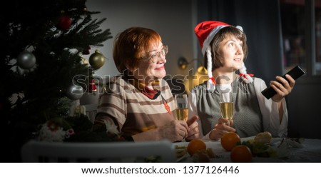 Happy mother and daughter drink champagne and watch TV on Christmas night