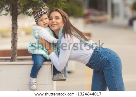 Happy mother and daughter have fun and wearing a jeans clothes in city. Street style family look. #1324644017