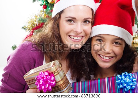 happy mother and daughter holding Christmas gifts