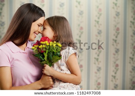 Happy Mother and daughter hugging  with flowers #1182497008
