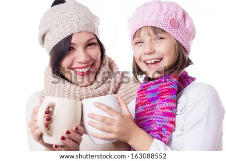 Happy mother and daughter in knitted hats with hot beverages over white