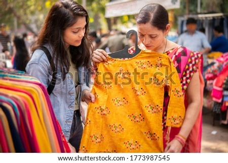 Happy mother and daughter looking and buying clothes together from outdoor street market of Delhi, India at day time. shoot location Sarojini  Nagar, Delhi, India.