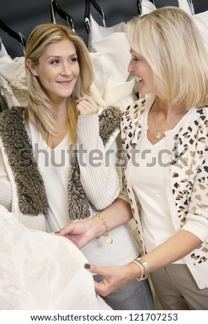 Happy mother and daughter looking at each other while selecting wedding dress in bridal boutique