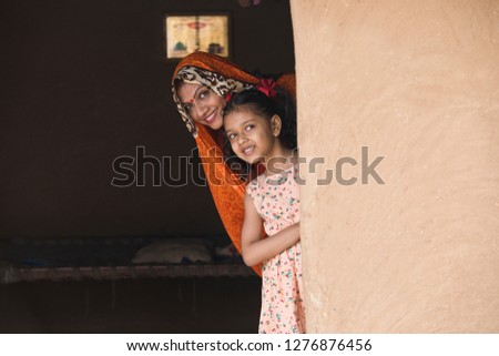Happy mother and daughter peeking from rural house #1276876456