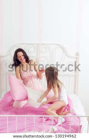 happy mother and daughter playing in bad - stock photo