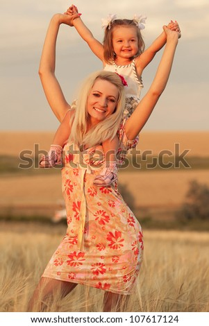happy mother and daughter playing on a wheat field