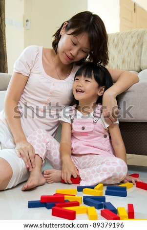 Happy mother and daughter playing with colorful blocks inside a house