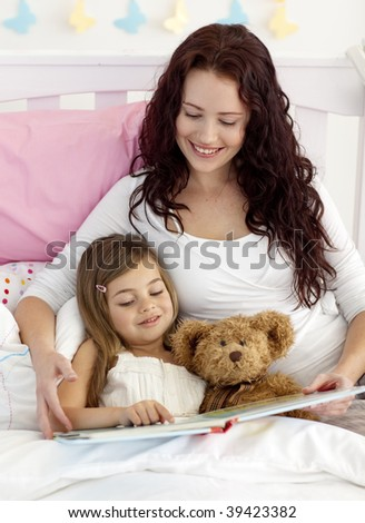 Happy mother and daughter reading a book together in bed - stock photo