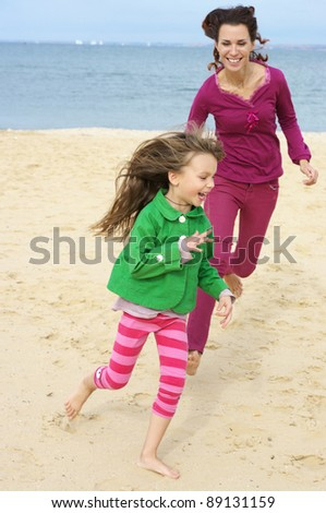 Happy mother and daughter running at beach.