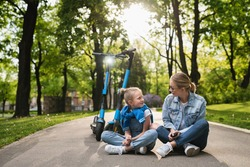 Happy mother and daughter sitting on a road after electric scooters ride