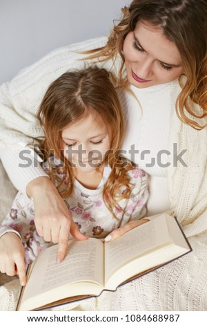 Happy Mother and daughter sitting on bed under plaid and reading book