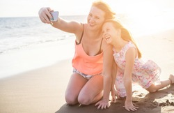 Happy mother and daughter taking selfie photo with smartphone on the beach - Mother having fun with her kid on holiday vacation - Family lifestyle concept - Sunset color tones filter