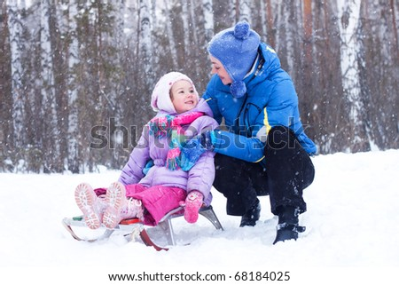 Happy mother and daughter, the family for a walk in a winter park, luge, skiing, skating, snowballs - stock photo