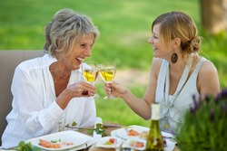 Happy mother and daughter toasting white wine at dining table in lawn