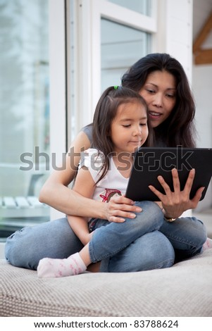 Happy mother and daughter using a digital tablet in a home interior, shallow depth of field with critical focus on child