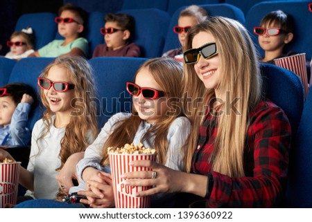 Happy mother and daughter wearing 3d glasses and eating tasty popcorn in cinema. Cheerful family watching funny film and enjoying spare time together in movie house. Concept of enjoyment and fun. #1396360922