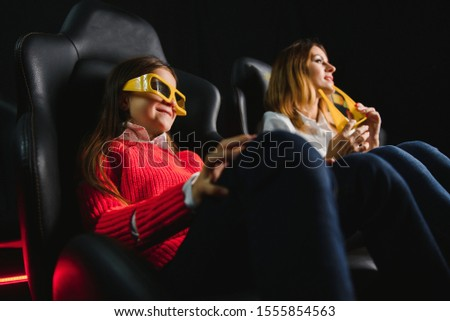 Happy mother and daughter wearing 3d glasses in cinema. Cheerful family watching funny film and enjoying spare time together in movie house. Concept of enjoyment and fun. #1555854563