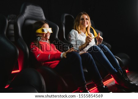 Happy mother and daughter wearing 3d glasses in cinema. Cheerful family watching funny film and enjoying spare time together in movie house. Concept of enjoyment and fun. #1555854569