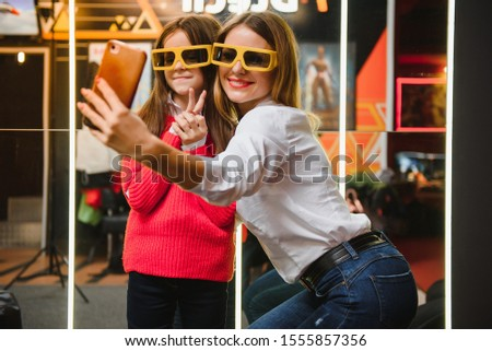 Happy mother and daughter wearing 3d glasses in cinema. Cheerful family watching funny film and enjoying spare time together in movie house. Concept of enjoyment and fun. #1555857356