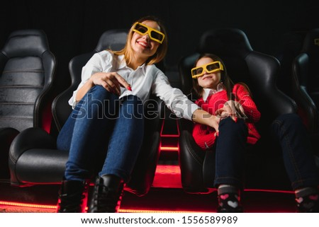 Happy mother and daughter wearing 3d glasses in cinema. Cheerful family watching funny film and enjoying spare time together in movie house. Concept of enjoyment and fun. #1556589989
