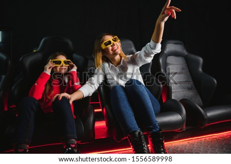 Happy mother and daughter wearing 3d glasses in cinema. Cheerful family watching funny film and enjoying spare time together in movie house. Concept of enjoyment and fun. #1556589998