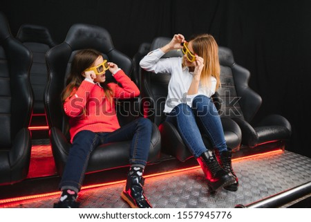 Happy mother and daughter wearing 3d glasses in cinema. Cheerful family watching funny film and enjoying spare time together in movie house. Concept of enjoyment and fun. #1557945776