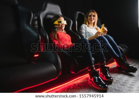Happy mother and daughter wearing 3d glasses in cinema. Cheerful family watching funny film and enjoying spare time together in movie house. Concept of enjoyment and fun. #1557945914