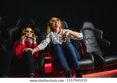 Happy mother and daughter wearing 3d glasses in cinema. Cheerful family watching funny film and enjoying spare time together in movie house. Concept of enjoyment and fun. #1557945935