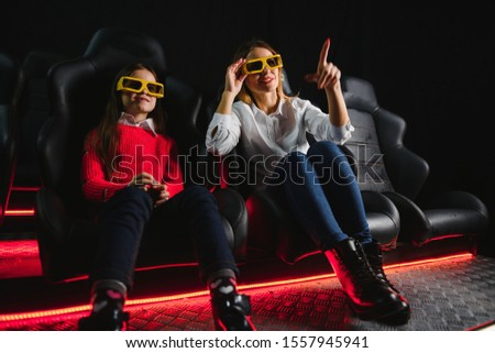 Happy mother and daughter wearing 3d glasses in cinema. Cheerful family watching funny film and enjoying spare time together in movie house. Concept of enjoyment and fun. #1557945941