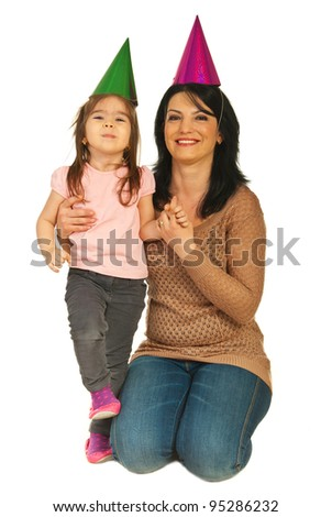Happy mother and daughter wearing party hats and sitting on floor isolated on white background