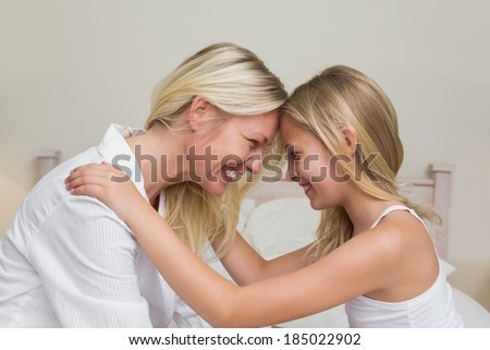 Happy mother and daughter with head to head in bedroom