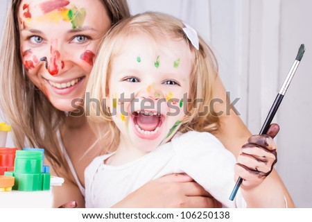 Happy mother and daughter with paint on faces, focus on baby