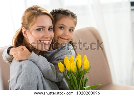 happy mother and daughter with yellow tulips hugging and smiling at camera #1020280096