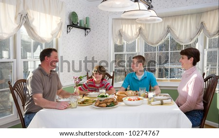 Happy mother and father and their teenage sons eating at the dinner table