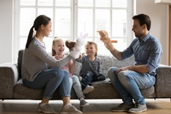 Happy mother and father holding fluffy toys, playing doll theatre with adorable little kids daughter and son sitting on cozy couch, family having fun, spending leisure time together in living room