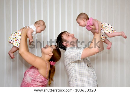 Happy mother and father raising and laughing with two tiny babies twin sisters girls
