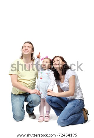 Happy mother and father sit down and embrace little daughter which points fingers up