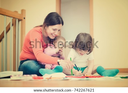Happy mother and her children drawing on paper #742267621