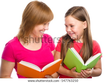 Happy mother and her daughter are reading books, isolated over white - stock photo