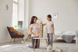 Happy mother and her daughter playing board game at home. Parent and child building tower from wooden blocks indoors