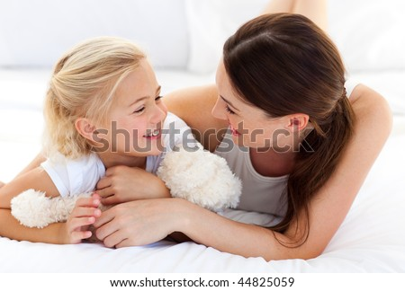 Happy mother and her daughter playing together lying on a bed