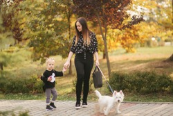 Happy mother and her daughter playing with dog in autumn park. Family, pet, domestic animal and lifestyle concept. Autumn time. Mother and daughter sitting on the bench