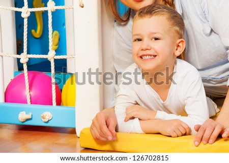 Happy mother and her five years old kid laying on the floor with just drawn picture