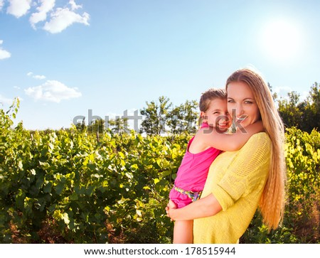 Happy mother and her little daughter in the harvest time in the vineyard