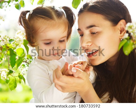 Happy mother and her little daughter in the spring day #180733592