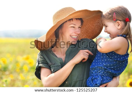 Happy mother and her little daughter in the sunflower field