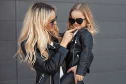 Happy mother and her little girl in same outfits: white t-shirts, leather black jackets and leggings, sunglasses. Family look: stylish mom with daughter