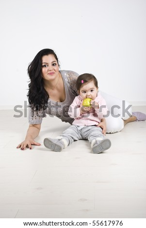 Happy mother and her little girl sitting on wooden floor and the baby holding and eating a green apple
