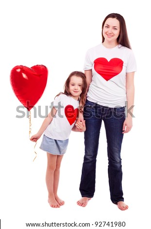 happy mother and her six year old daughter wearing T-shirts with big red hearts and holding a heart-shaped balloon, isolated against white background