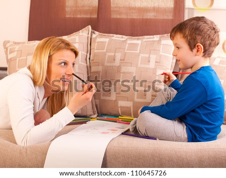 Happy mother and her son drawing together.